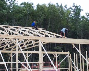 Pole barn construction workers working on roof