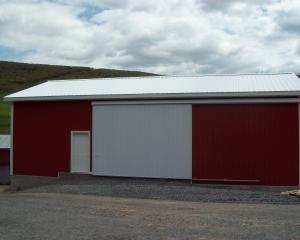 red agricultural pole barn with white trim, white roof, and white doors