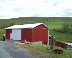 red agricultural pole barn with white trim, doors, and roof