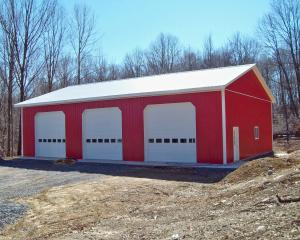 Red pole building garage with white roof and trim and three garage doors