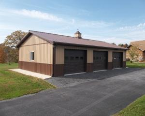 Two tone brown pole barn garage with three garage doors and cupola