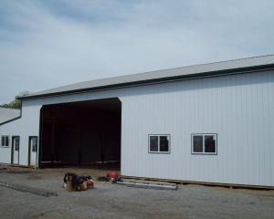 white agricultural pole barn with large garage door opening