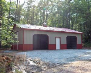 Tan two car pole barn garage with red skirting and trim