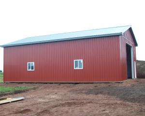red agricultural pole barn with green trim and white doors