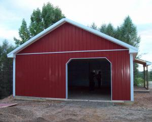 Red agricultural pole barn with white trim and porch