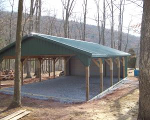 Post frame pavilion with green roof, rear wall, and stone floor
