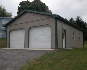 Clay and green pole building garage with two garage doors