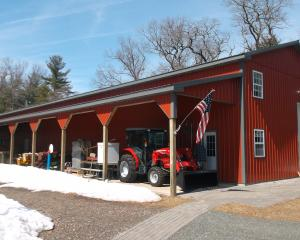 Red agricultural pole barn with dark gray trim and lean to on the the side