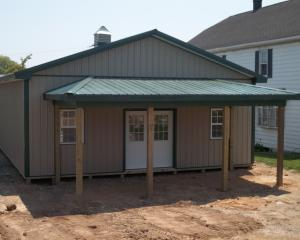 Brown commercial pole building with green roof and trim and a porch on the front