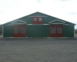 Green horse pole barn with red doors