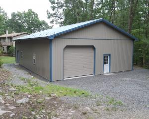 Clay pole building garage with blue trim and roof