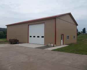 Brown pole building garage with red trim
