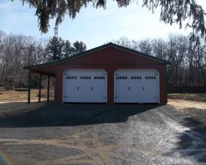 Red two car pole barn garage with black trim